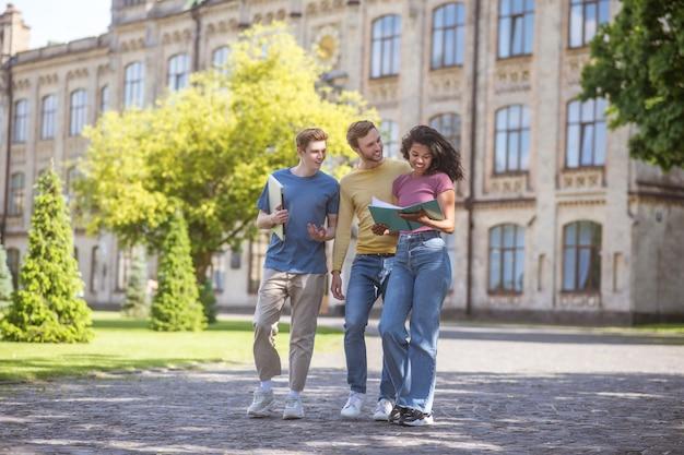 Estudiantes. dos chicos y una chica caminando y discutiendo futuros exámenes.