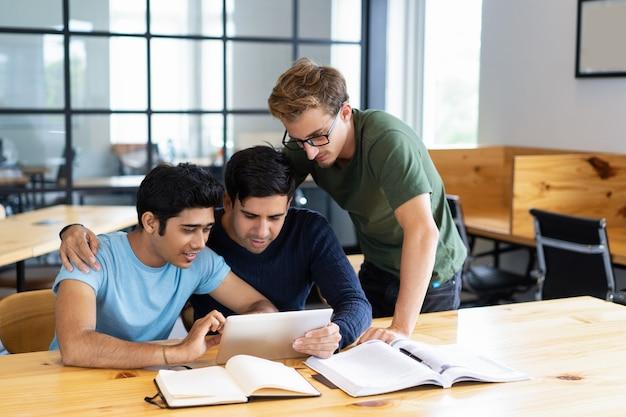 Estudiantes enfocados que navegan en la tableta y hablan