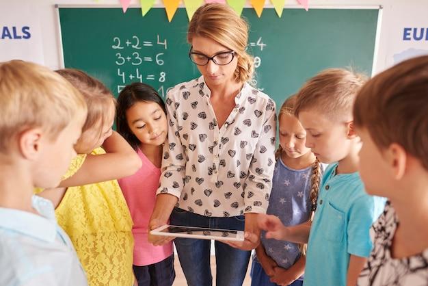 Estudiantes enfocados en tableta digital