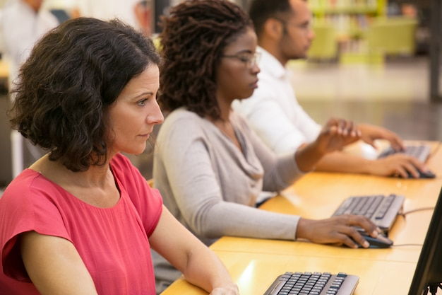 Estudiantes enfocados trabajando con computadoras en la biblioteca