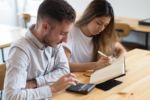 Estudiantes enfocados usando calculadora y estudiando juntos
