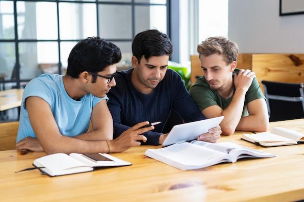 Estudiantes enfocados usando tabletas y discutiendo información