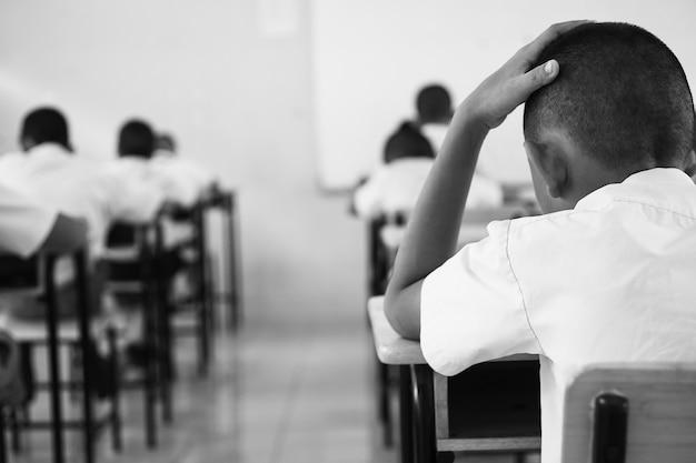 Los estudiantes escriben y leen ejercicios de hojas de respuesta de exámenes en el aula de la escuela con estrés.
