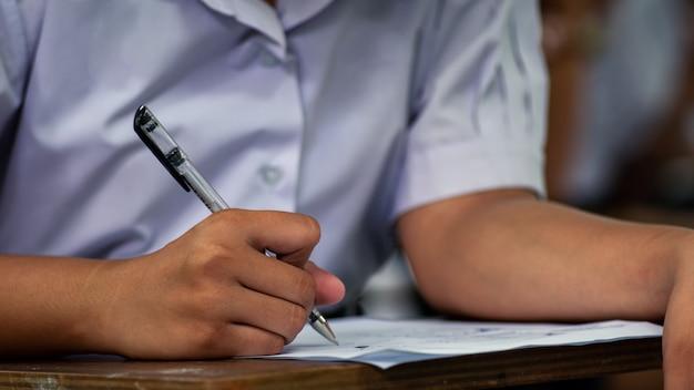 Estudiantes escribiendo y leyendo ejercicios de hojas de respuestas de exámenes en el aula de la escuela con estrés