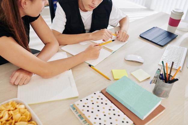 Estudiantes de la escuela de adolescentes sentados en una mesa grande y discutiendo ideas para el ensayo del proyecto escolar