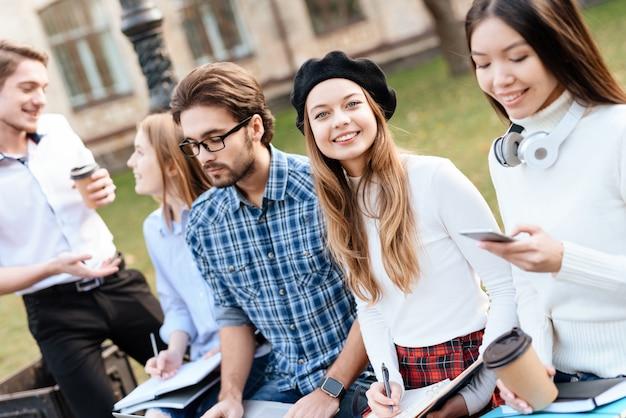 Los estudiantes están sentados y estudiando juntos en la universidad.