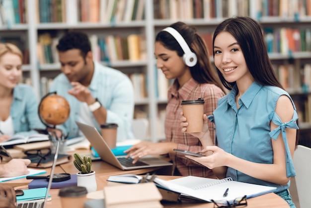 Los estudiantes están sentados a la mesa en la biblioteca.