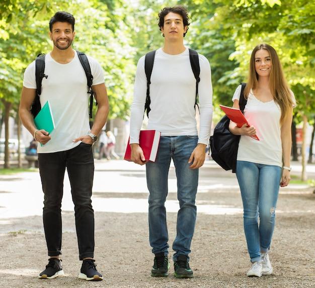 Estudiantes felices al aire libre sonriendo de cuerpo entero