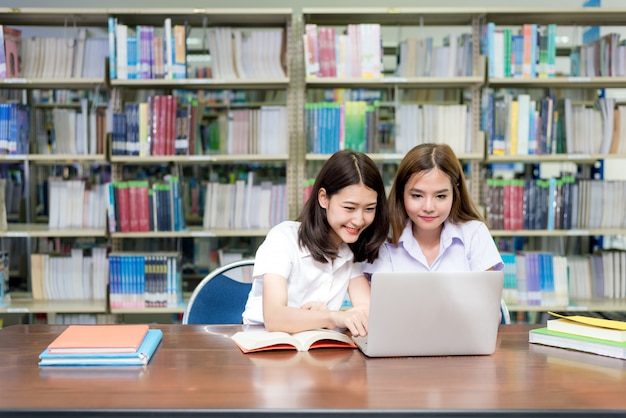 Estudiantes felices asiáticos con ordenador portátil trabajando y estudiando en la biblioteca.