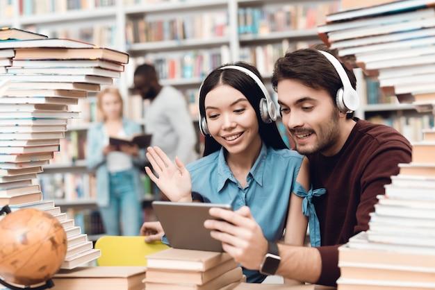 Los estudiantes felices están usando tableta con auriculares.