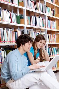 Estudiantes felices con el portátil en la biblioteca