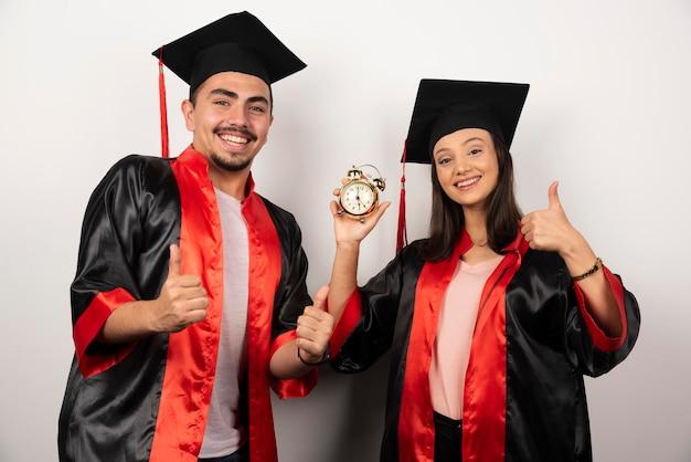 Estudiantes felices en vestido con pie de reloj en blanco.