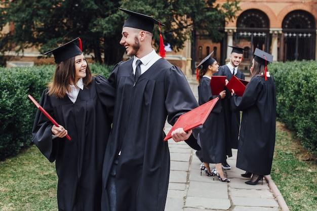 Estudiantes felices en vestidos de graduación en el campus universitario estilo de vida