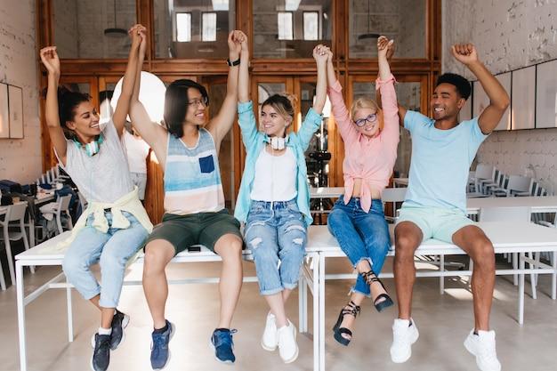 Los estudiantes se felicitan entre sí por el final del año escolar. los amigos de la universidad están felices de haber aprobado los exámenes finales y saludando con la mano.