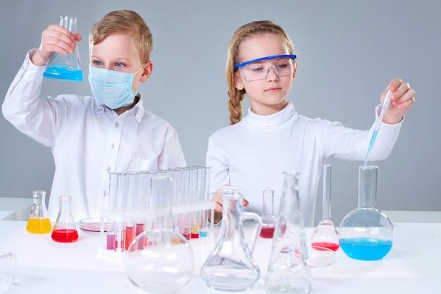 Los estudiantes con frascos para experimentos químicos