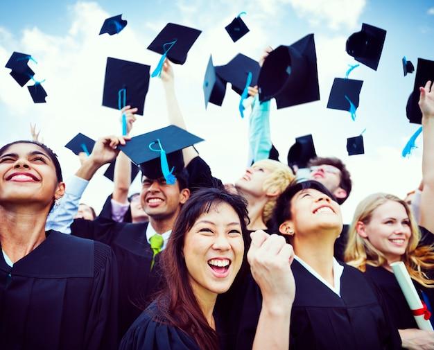 Estudiantes graduados arrojando sombreros en el aire