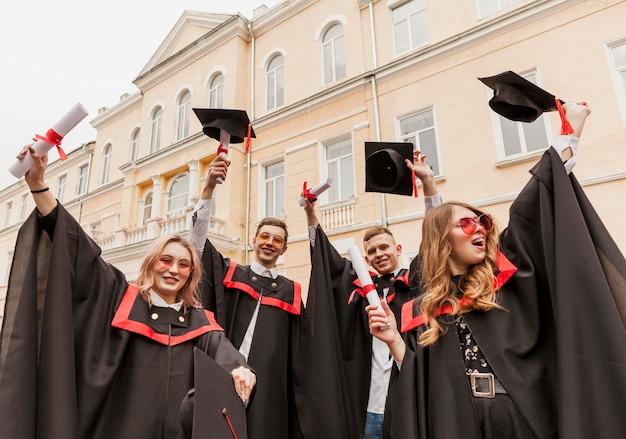 Estudiantes graduados felices de ángulo bajo