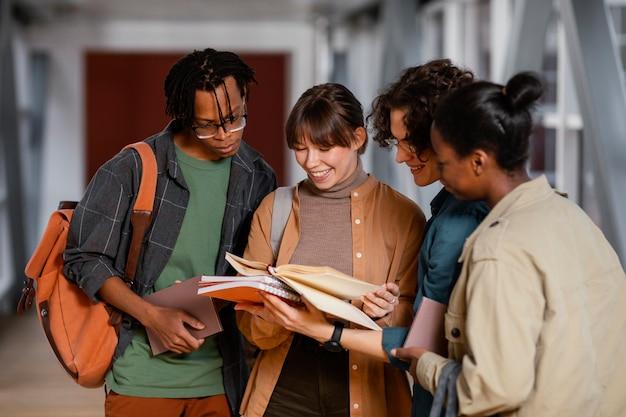Estudiantes hablando de un proyecto en el pasillo.