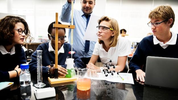 Estudiantes haciendo un proyecto de experimento de ciencia con un maestro