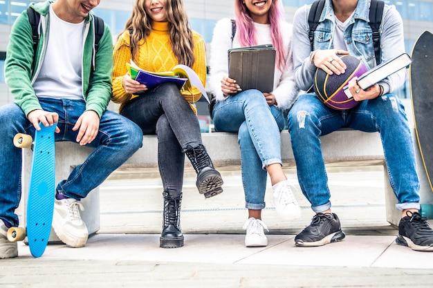 Estudiantes haciendo proyecto grupal sentados en el campus universitario.