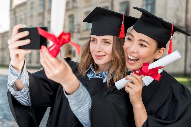 Estudiantes haciendo selfie en su graduación