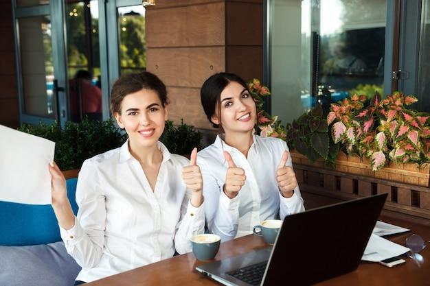 Estudiantes hermosos jóvenes felices usando laptop y tomando café en la cafetería al aire libre. pulgares hacia arriba