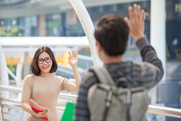 Los estudiantes de hombre y mujer con muchos libros agitando las manos saludan a sus amigos