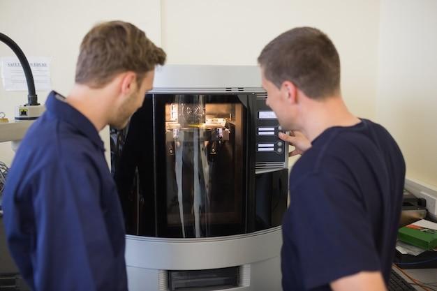 Estudiantes de ingeniería que usan una impresora 3d