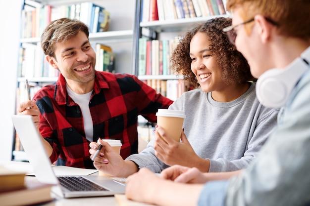 Estudiantes interculturales felices en ropa casual discutiendo videos en línea mientras toman café en la biblioteca