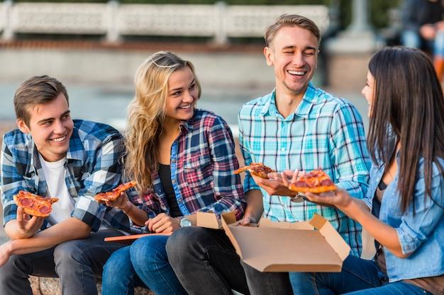 Los estudiantes jóvenes divertidos, están comiendo pizza grande.
