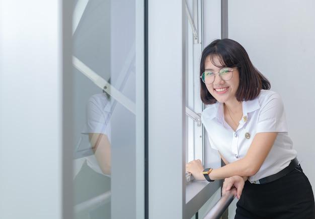 Los estudiantes jovenes felices en uniforme sonríen cerca de la ventana, concepto de la educación