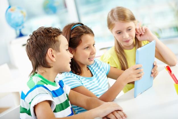 Estudiantes jugando con una tableta digital Foto gratis