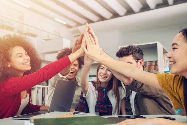 Los estudiantes juntan sus manos en la oficina
