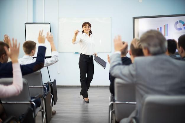 Estudiantes levantando la mano para hacer preguntas durante el seminario
