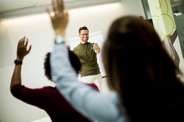 Estudiantes levantando la mano para responder a la pregunta durante el taller de capacitación.