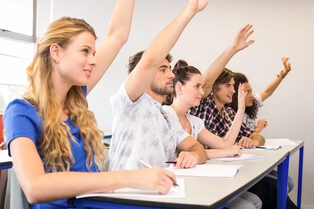 Estudiantes levantando las manos en el aula