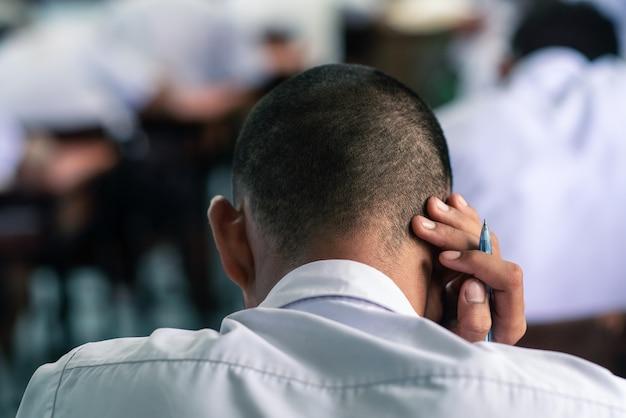 Estudiantes leyendo ejercicios de hojas de respuestas de exámenes en el aula de la escuela con estrés