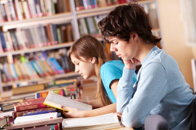 Estudiantes leyendo libros y preparando el examen