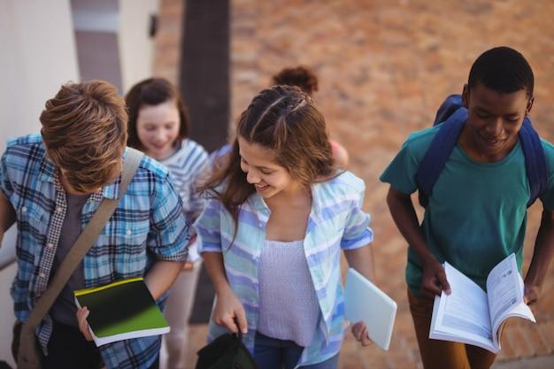 Estudiantes con libros y tableta digital caminando por el campus de la escuela