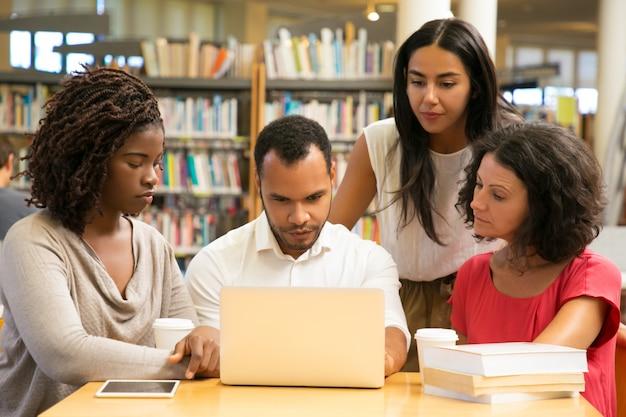 Estudiantes maduros serios que trabajan con una computadora portátil en la biblioteca pública
