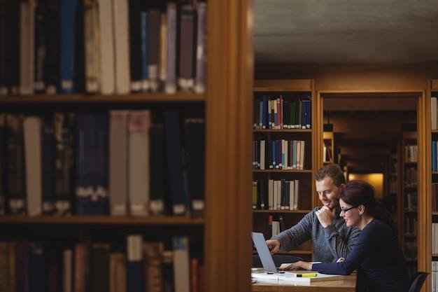 Estudiantes maduros trabajando juntos en la biblioteca de la universidad