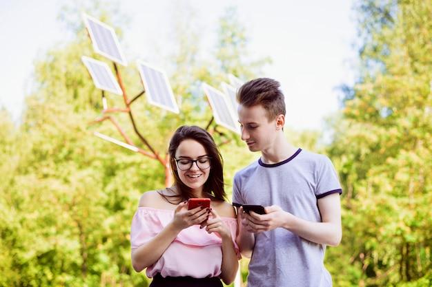 Estudiantes masculinos y femeninos contra paneles solares usando dispositivos modernos