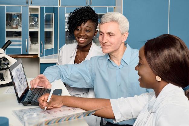 Estudiantes de medicina africanos muestran datos actualizados sobre el líder del grupo masculino caucásico europeo senior sobre la vacuna contra el nuevo coronavirus sars-cov-2