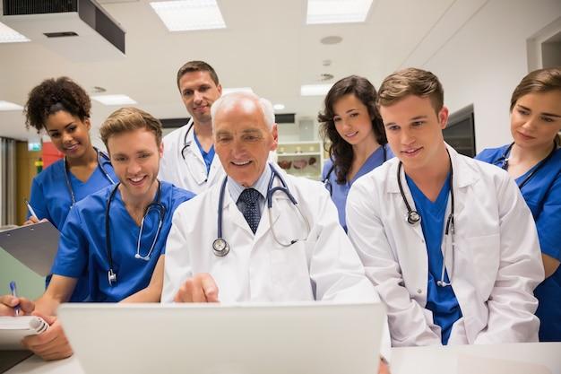 Estudiantes de medicina y profesor usando laptop