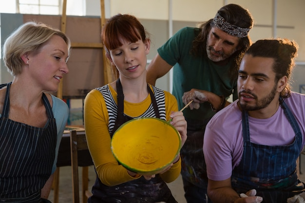 Estudiantes mirando al profesor pintando maceta