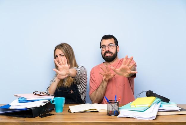 Estudiantes con muchos libros nerviosos estirándose las manos hacia delante.