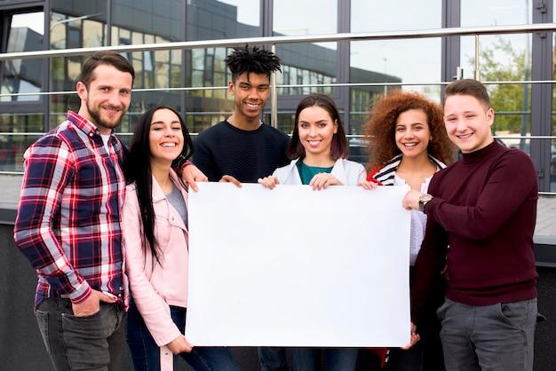 Estudiantes multiétnicos sonrientes que sostienen el cartel blanco en blanco que se coloca delante del edificio de cristal