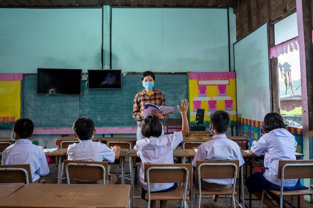 Los estudiantes de niños asiáticos usan mascarilla de aprendizaje en el aula en la escuela primaria, el estudiante levanta la mano para responder las preguntas que los maestros les hacen