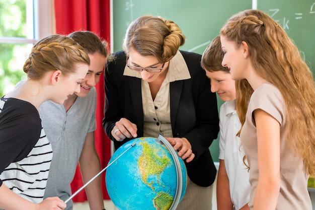 Estudiantes o alumnos que tienen trabajo en grupo mientras la lección de geografía y el maestro los evalúan o educan en la escuela o clase.