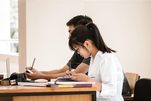 Los estudiantes o personas de negocios asiáticos trabajan estudiando junto con el cuaderno de documentos y los papeles en la oficina moderna, discuten el archivo de informes de la solución de marketing de finanzas en las oficinas ocupadas. concepto de reunión de trabajo en equipo